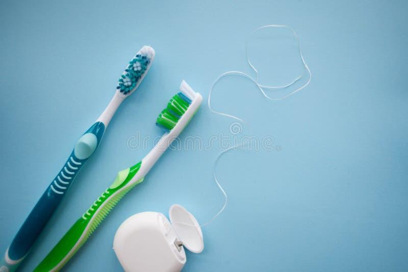 两把牙刷和牙线在蓝色背景 免版税图库摄影