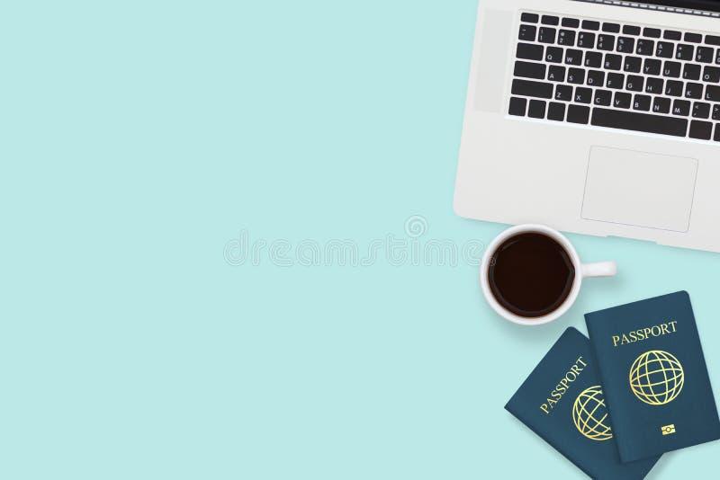 两护照、咖啡杯和计算机膝上型计算机平的位置在淡色蓝色背景与拷贝空间 旅行,签证 库存照片