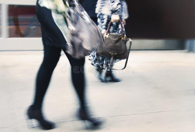 两拿着设计师提包和佩带高跟鞋的妇女 免版税库存图片