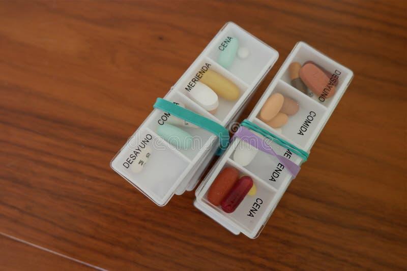 两捆绑有不同颜色片剂每日药量的箱子  图库摄影