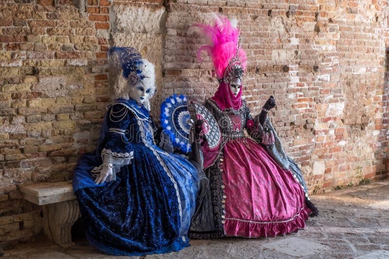 两掩没了妇女坐一条石长凳在威尼斯狂欢节期间 库存照片