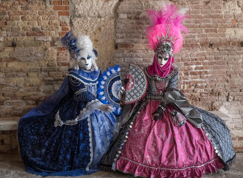 两掩没了妇女里面坐一条石长凳在威尼斯狂欢节期间 免版税库存照片