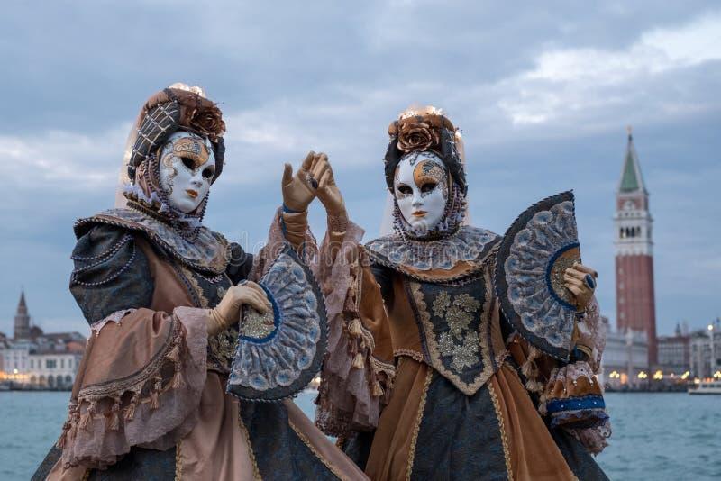 两掩没了服装的妇女有装饰的爱好者的,在有圣后边标记正方形和钟楼的圣乔治, 免版税库存照片