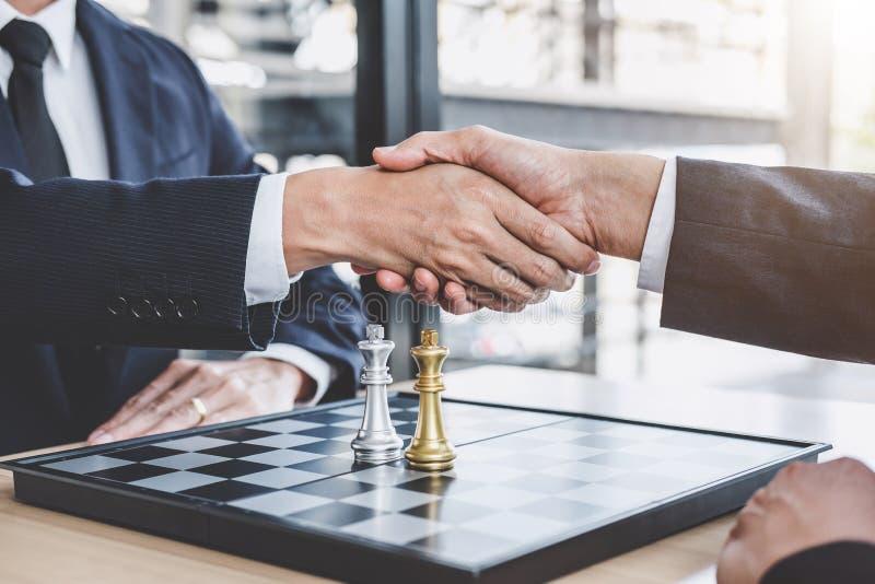 两握手的商人在演奏下棋比赛伸手可及的距离的末端以后 图库摄影