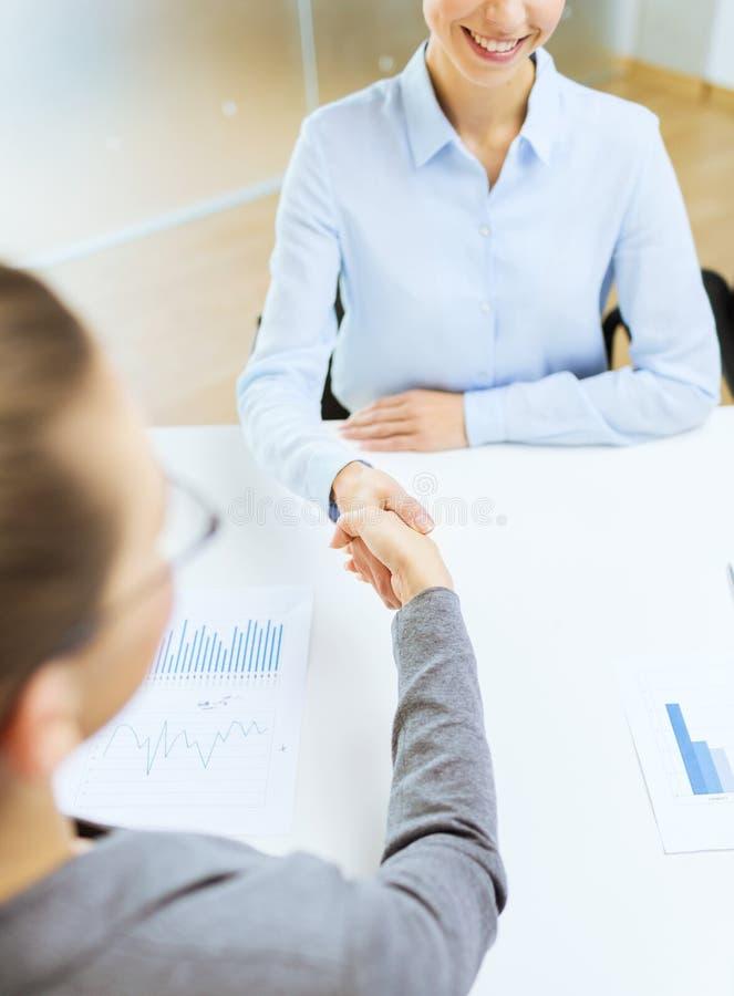 两握手的微笑的女实业家在办公室 免版税库存图片