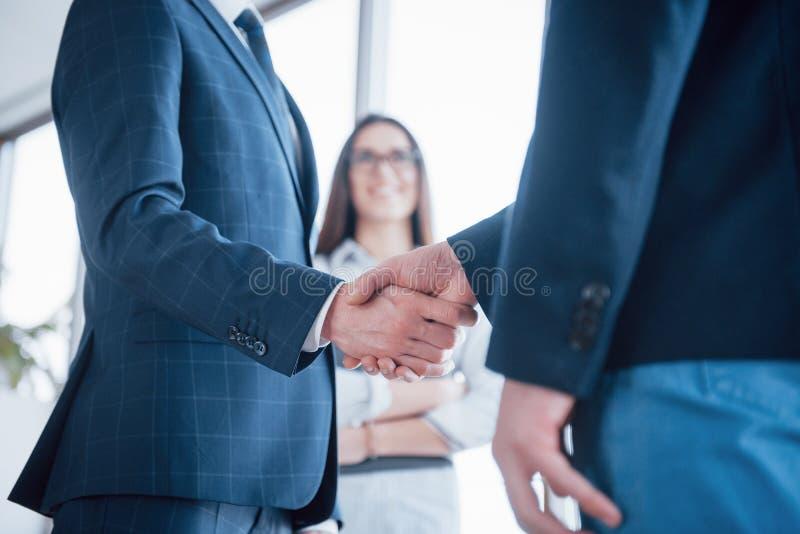 两握手的确信的商人在一次会议期间在办公室,成功,成交,招呼和伙伴概念 库存照片