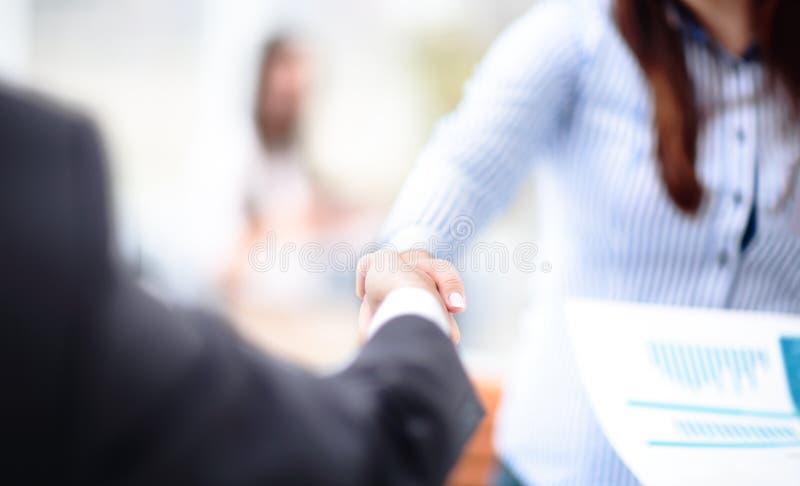 两握手的确信的商人在一次会议期间在办公室,成功,成交,招呼和伙伴概念 库存图片