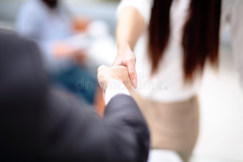 两握手的确信的商人在一次会议期间在办公室,成功,成交,招呼和伙伴概念 免版税库存照片