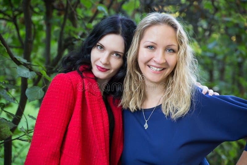 两摆在绿色公园的微笑的妇女 库存照片