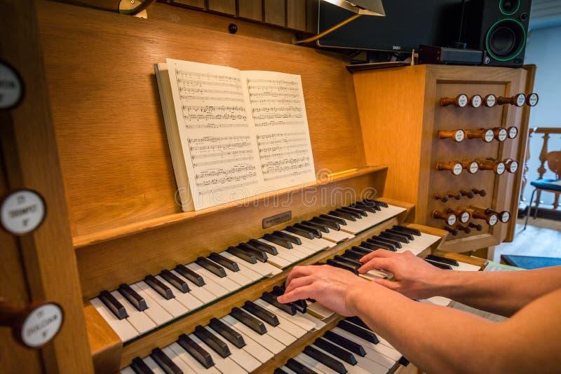 两播放一种教会器官的手在Kristkirken 免版税库存图片