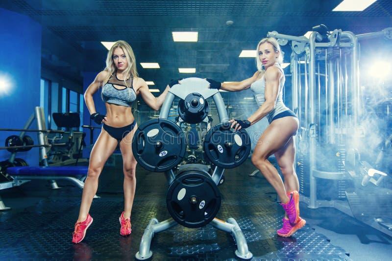 两放松在健身房的肌肉性感的健身妇女妇女 概念健康生活方式 爱好健美者在体操里 图库摄影