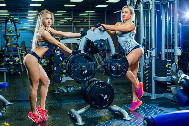 两放松在健身房的肌肉性感的健身妇女妇女 概念健康生活方式 爱好健美者在体操里 库存照片