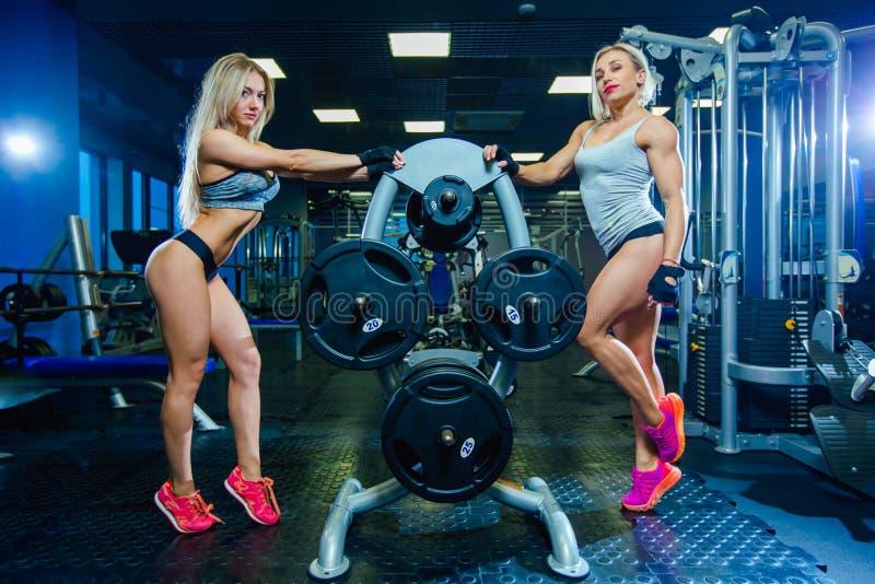 两放松在健身房的肌肉性感的健身妇女妇女 概念健康生活方式 爱好健美者在体操里 免版税库存照片