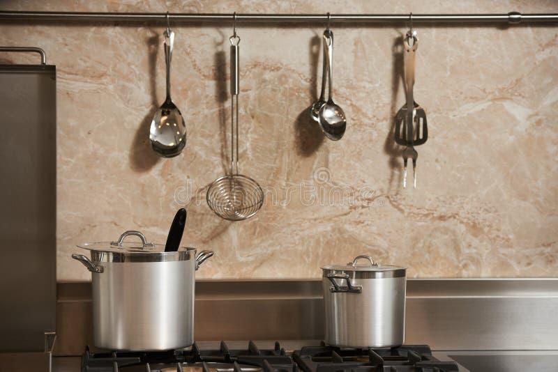 两新的金属平底深锅在气体滚刀的厨房里 免版税图库摄影