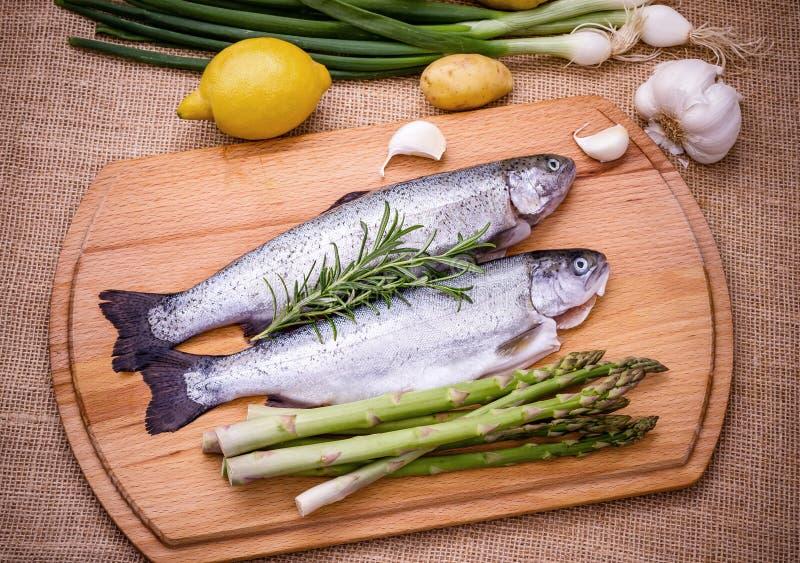 两未加工的鳟鱼用绿色芦笋、柠檬和大蒜 库存照片