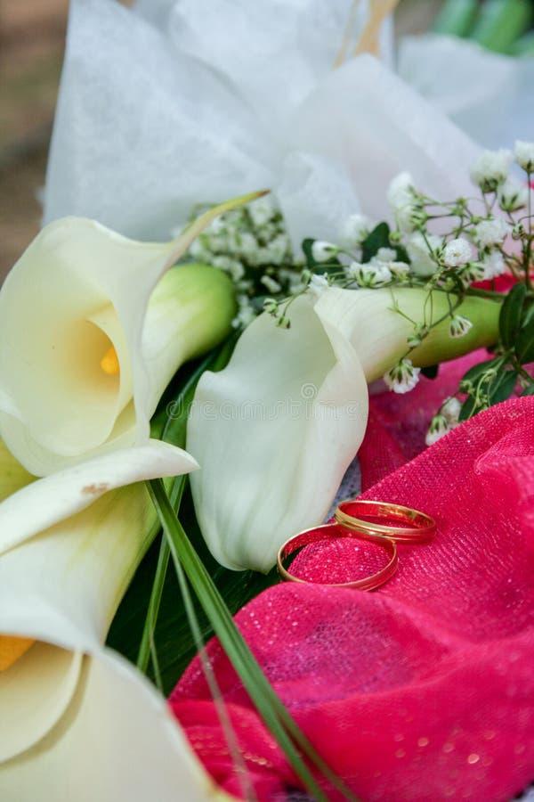 两朵婚戒和花静物画与丝绸装饰物 图库摄影
