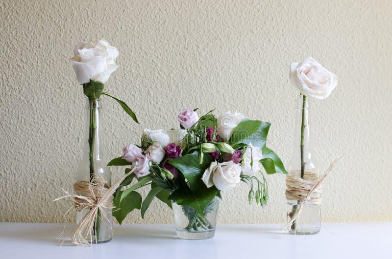 两朵白玫瑰和一块玻璃与更多玫瑰 库存照片