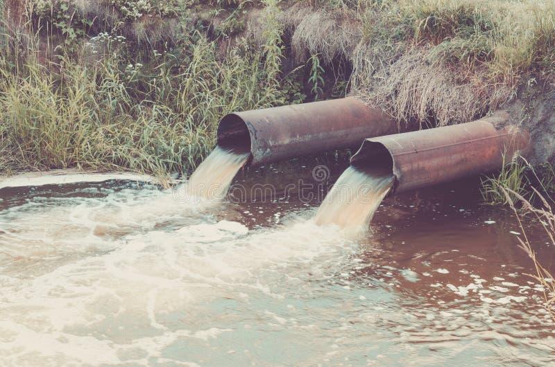 两条下水道倾吐到倾销废水的河/工业管子入河 ??? 免版税库存图片