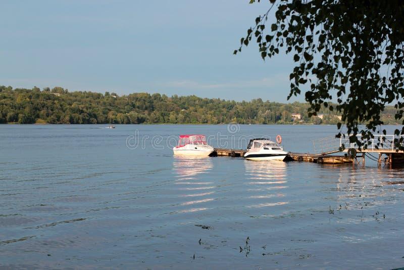 两条小船被栓对码头 在河的美好的金黄日落 美好的自然 免版税库存图片