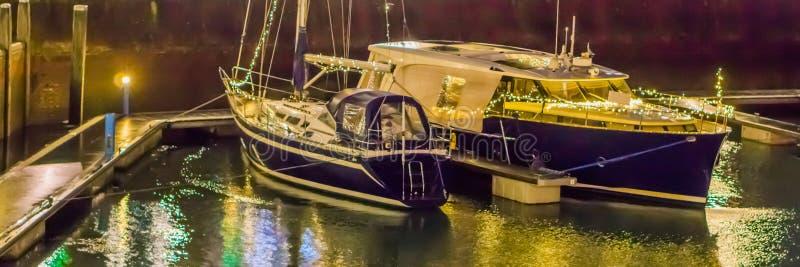 两条靠码头的小船在用光装饰的港口 库存图片