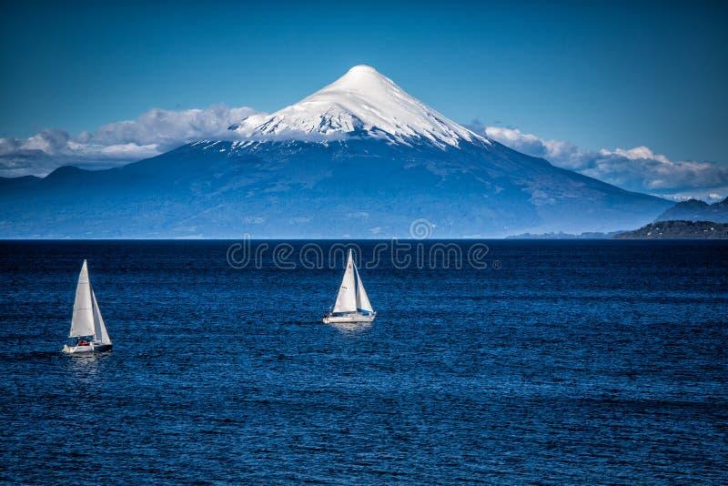 两条风船在雪加盖的Orsono火山前面航行在智利 免版税库存照片
