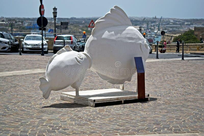两条鱼一个美好的石雕塑在瓦莱塔马耳他中间的 库存图片