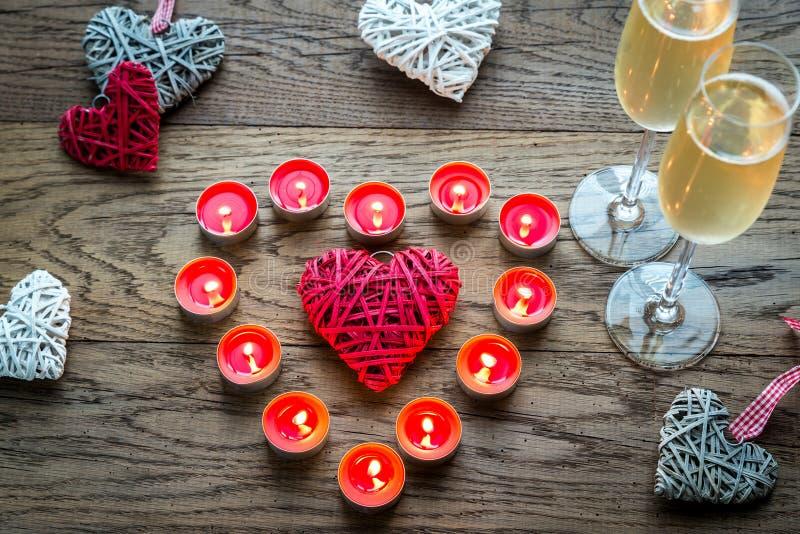两杯与灼烧的蜡烛和藤茎心脏的香槟 免版税库存图片