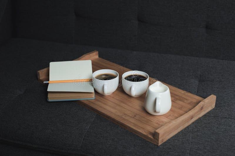 两杯咖啡、有铅笔的水罐牛奶和笔记本在木盘子 库存图片