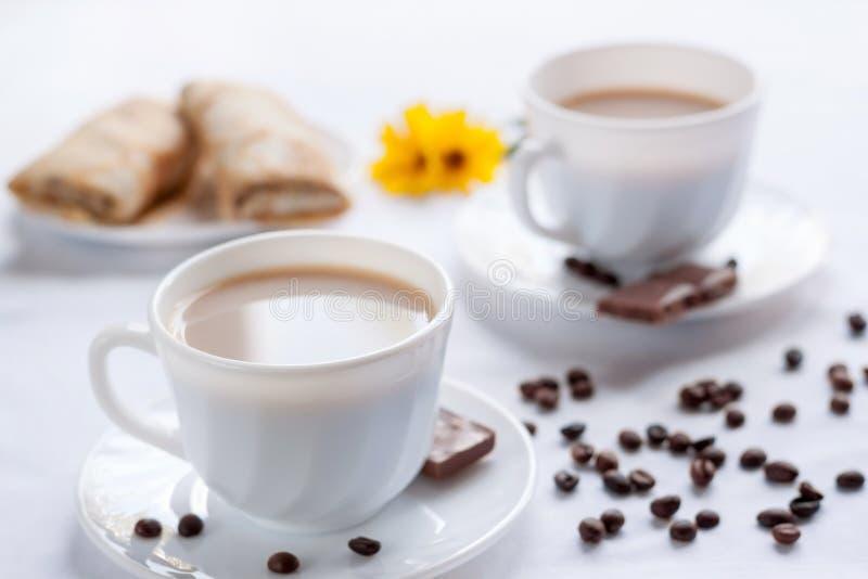 两杯咖啡、薄煎饼用果酱和牛奶巧克力 两的早晨早餐 库存图片