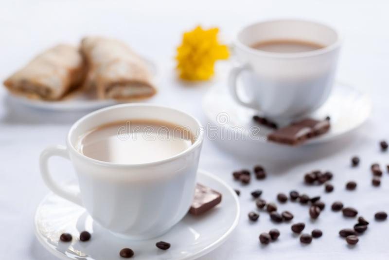 两杯咖啡、薄煎饼用果酱和牛奶巧克力 两的早晨早餐 库存照片