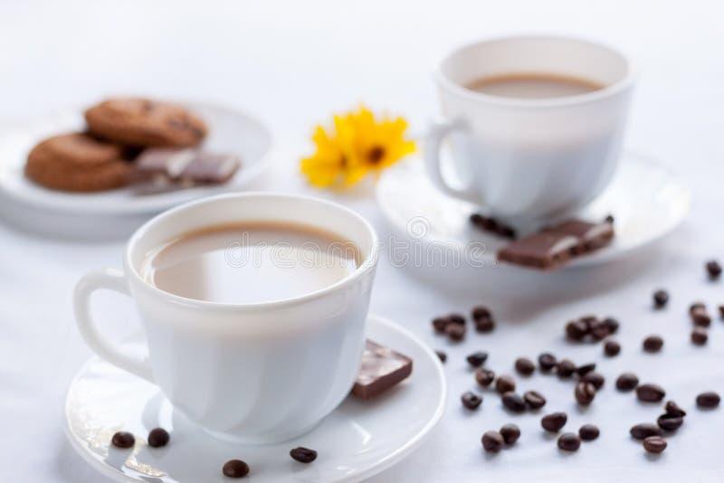 两杯咖啡、麦甜饼和牛奶巧克力 两的早晨早餐 免版税库存图片