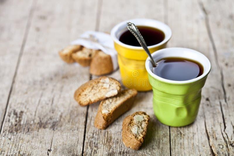 两杯咖啡和新鲜的意大利曲奇饼cantuccini与杏仁坚果在ructic木桌背景 库存照片