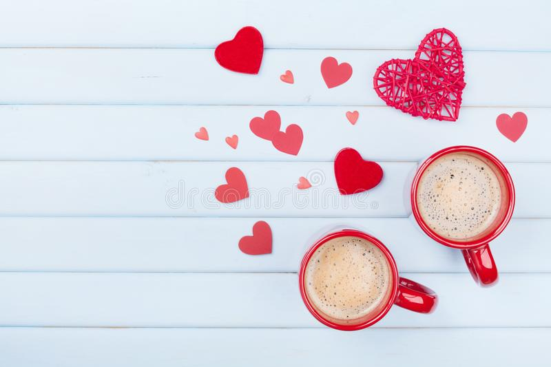 两杯咖啡和混杂的心脏在淡色蓝色台式视图 早晨早餐为情人节 概念亲吻妇女的爱人 免版税库存图片