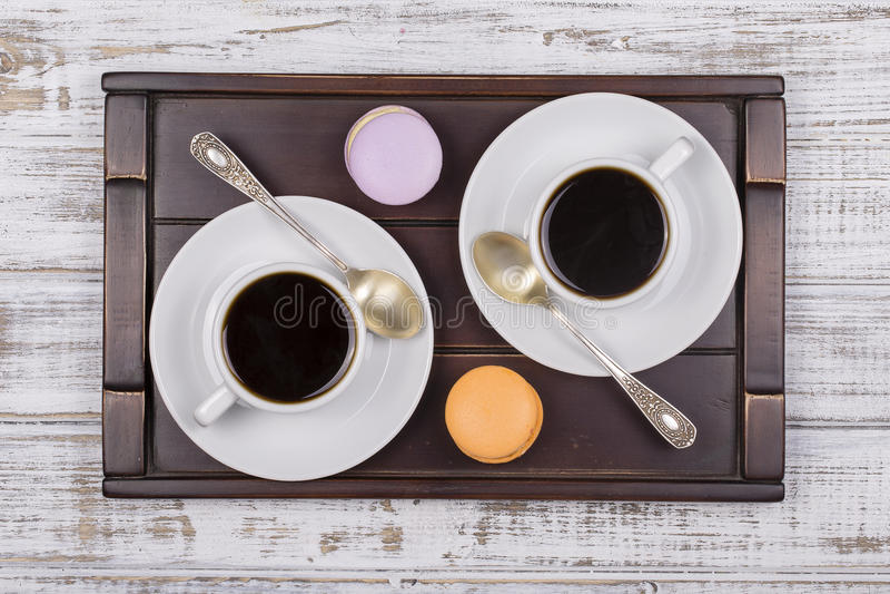 两杯咖啡在盘子的、匙子和macaron蛋糕在白色木桌上 生活方式概念 顶视图 图库摄影