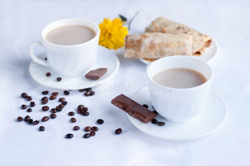 两杯咖啡用牛奶、薄煎饼用果酱和牛奶巧克力 两的早晨早餐 免版税图库摄影