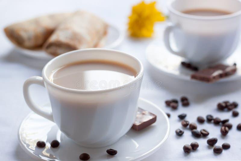 两杯咖啡用牛奶、薄煎饼用果酱和牛奶巧克力 两的早晨早餐 库存图片
