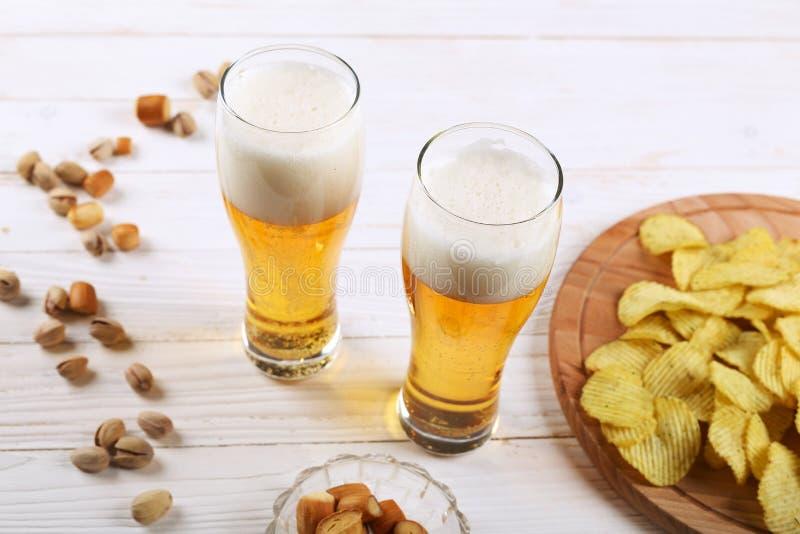 两杯啤酒和快餐在一张白色木桌上 芯片,开心果,干乳酪 库存照片