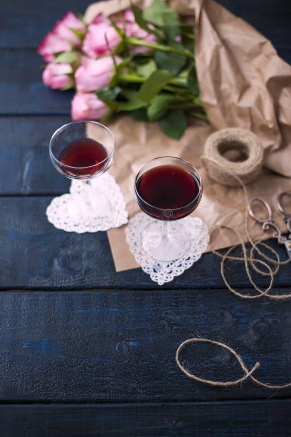 两杯在一张黑暗的桌,桃红色玫瑰花束上的红葡萄酒在包装纸的 两个白色心脏和通心面饼干 自由 库存图片