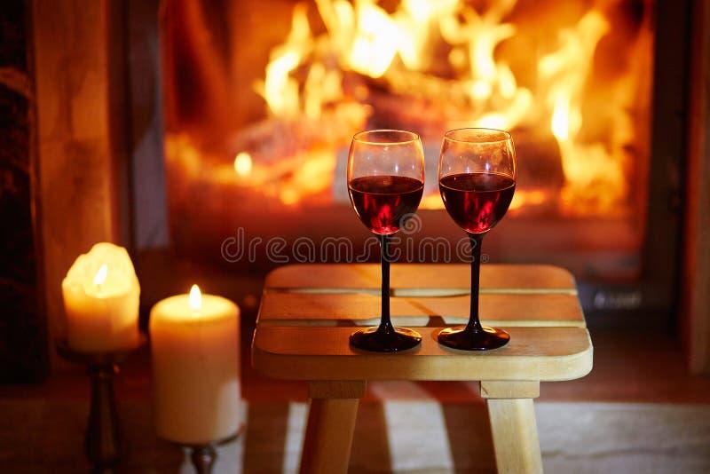 两杯在壁炉附近的红葡萄酒 免版税库存图片