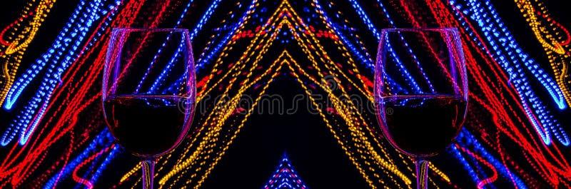两杯在摘要背景的酒上色了在行动的光 光多彩多姿的线在黑背景的 免版税库存照片