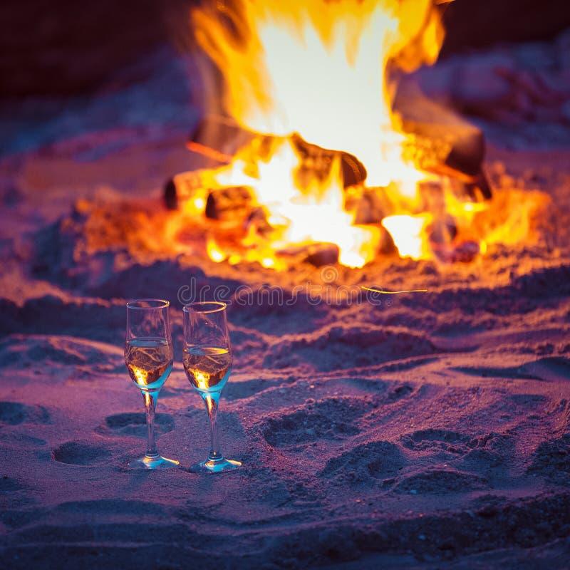 两杯在温暖的壁炉前面的汽酒在海的沙子 免版税图库摄影
