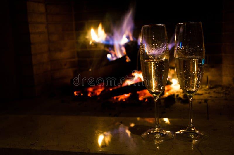 两杯在灼烧的壁炉附近的香槟 库存图片
