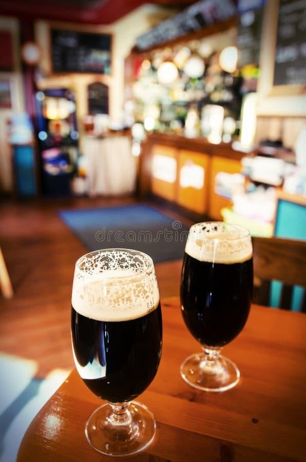 两杯在酒吧的黑啤酒 免版税图库摄影