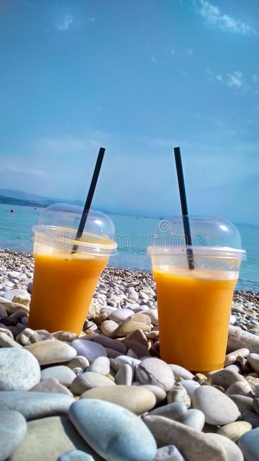 两杯在Pebble海滩的新鲜的橙汁 库存照片