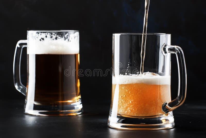 两杯德国低度黄啤酒,啤酒涌入了杯子,黑暗的酒吧柜台,选择聚焦 免版税库存图片