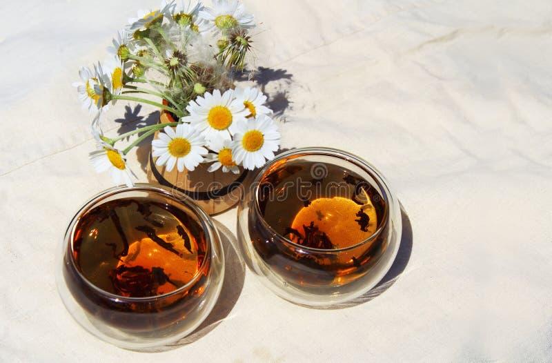 两杯甘菊茶和春黄菊花束  库存图片