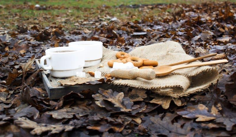 两杯白色茶和火在背景 两木匙子和糖用百吉卷在用麻袋布盖的木桌上 库存图片