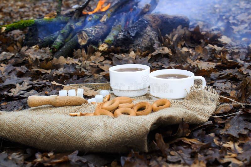 两杯白色茶和火在背景 两木匙子和糖用百吉卷在用麻袋布盖的木桌上 库存照片
