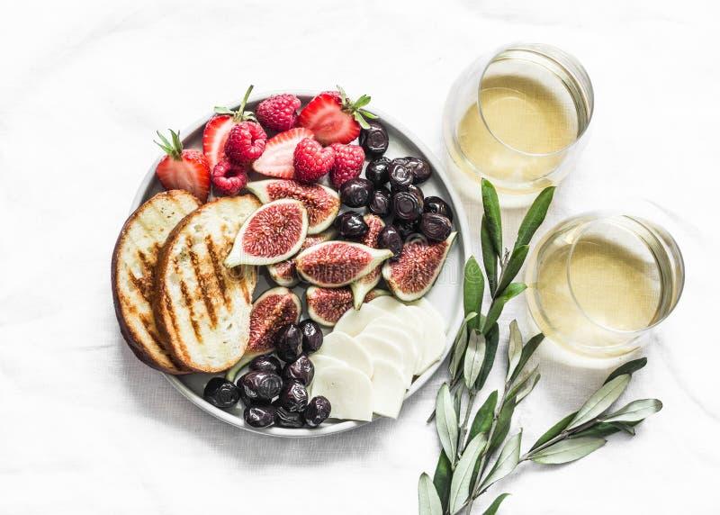 两杯白葡萄酒和零食开胃小吃盘,配有奶酪、无花果、橄榄、淡背景的浆果,俯视 免版税库存照片