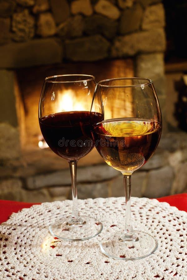 两杯红色白葡萄酒,壁炉烟囱背景 浪漫xmas明信片,一个xmas晚上的舒适内部 库存图片